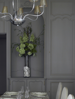 Grey panelled dining room with chandelier and flower arrangement in recess in Paris apartment, France