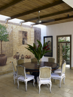 Cut flowers on dining table with chairs next to fresco on wall of covered terrace of a residential home in Sri Lanka.