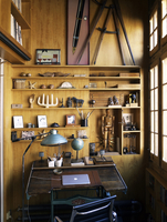 Computer desk with lap top and lamp next to shelves of wooden ornaments in Spanish residential home.