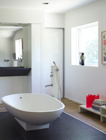 Modern freestanding bathtub and uncurtained window in bathroom of residential house, Denmark.