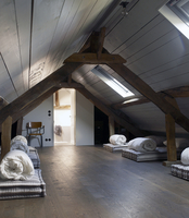 Sky lighted beamed loft space with multiple mattresses and rolled duvet with open door to bathroom in residential house, France. 25937008439| 写真素材・ストックフォト・画像・イラスト素材|アマナイメージズ