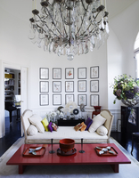 Japanese low table and chaise long in curved wall with mounted framed photos with crystal chandelier residential house, France.