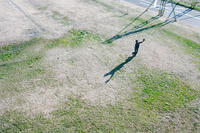 河川敷グランドで野球ボールで遊ぶ初老男性の遠景