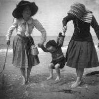 Perros-Guirec, deux jeunes filles, pieds nus dans la mer, font sauter la petite Madeleine