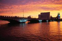 夕焼けの信濃川とライトアップされた萬代橋