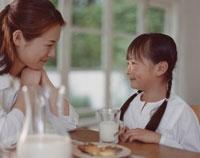 牛乳を飲みながら話をする母と娘