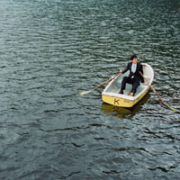 ボートに乗ってリラックスするビジネスマン