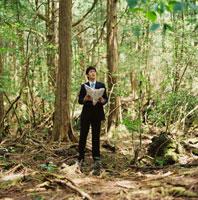 森林で地図を広げるビジネスマン