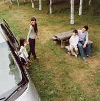 車から降りる母と娘を見守る父と息子