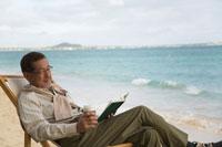 浜辺でリクライニングチェアに座り本を読むシニア男性