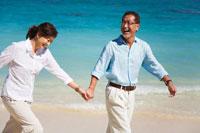 海辺で妻の手を引いてはしゃぐシニア男性 30003000470| 写真素材・ストックフォト・画像・イラスト素材|アマナイメージズ