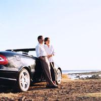 車の前で夕日に照らされる日本人シニア夫婦