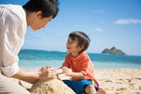 海辺で砂遊びをする日本人の父と息子