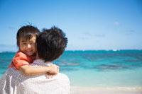 海辺で父親に抱きかかえられる息子