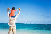 海辺で肩車をする父と息子の後姿