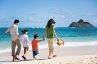 海辺を歩く日本人家族の後姿