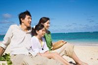 海辺に座って遠くを眺める日本人家族