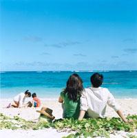 海で砂遊びをする姉弟を見つめる日本人夫婦 30003000596| 写真素材・ストックフォト・画像・イラスト素材|アマナイメージズ