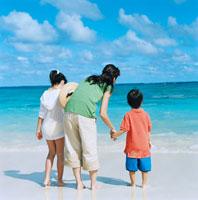 海辺で遠くを眺める母と姉弟の後姿