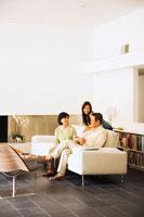 リビングでくつろぐ日本人シニア夫婦と娘