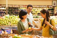 スーパーで買い物をする日本人のシニア夫婦と娘