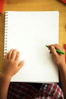 絵を描こうとする日本男の子の手元とノート