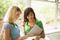 窓際でノートを見る若い日本人女性と白人女性