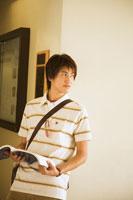 廊下で本を見る若い日本人男性