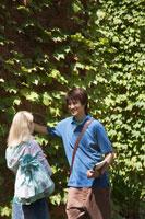 キャンパスで話す若い日本人男性と白人女性 30003001063  写真素材・ストックフォト・画像・イラスト素材 アマナイメージズ