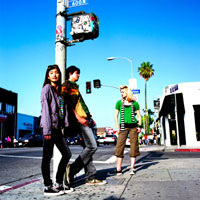 歩道にたたずむ若い日本人男女と白人女性