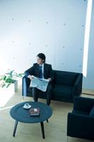 ソファで新聞を読むビジネスマン