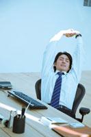 オフィスで伸びをするビジネスマン