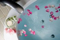 花びらを浮べた浴槽に置かれた蝋燭と花