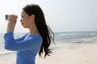 海で双眼鏡を覗く女性