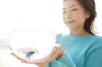 魚の入った鉢を持っている女性