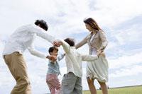 公園で手をつないで回る家族