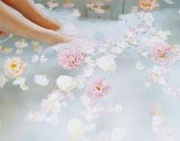 花を浮かべたバスタブと女性の足