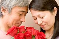 赤い花束を持つ日本人男性と日本人女性