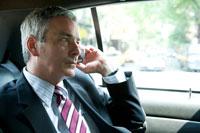 タクシーで携帯で話す白人男性
