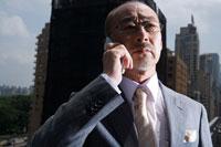 屋上で携帯で話す日本人ビジネスマン