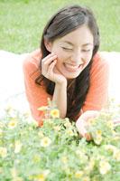 草原に寝転がり花を触る女性
