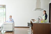 ソファに座る夫とキッチンに立つ妻
