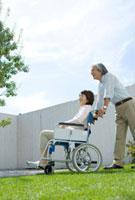 庭で車いすに座る妻を支える夫