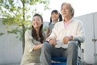 笑顔の車いすの祖父と母と娘