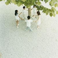 木の周りで手をつないで輪になる3人の女の子と2人の男の子
