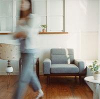 ソファのある部屋と歩く女性