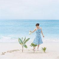 海辺で水をやる女性 30007000511| 写真素材・ストックフォト・画像・イラスト素材|アマナイメージズ