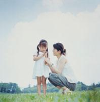 草原で花占いをする母と娘