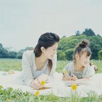 草原に寝転んで笑う母と娘