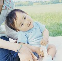 草原に座って笑う赤ちゃんと寄り添う母親